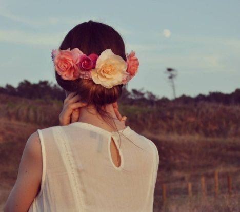 brunette woman with her hair in a rolled gibson tuck updo with flowers