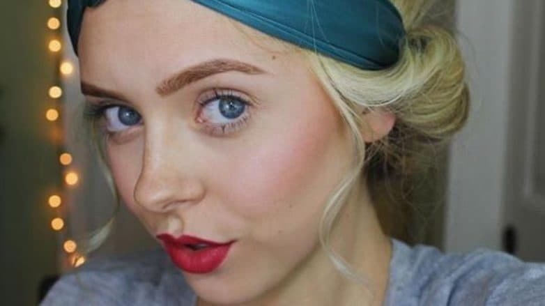 updos for short hair: close up of a blonde woman wearing a teal blue headband with her hair in a tucked updo