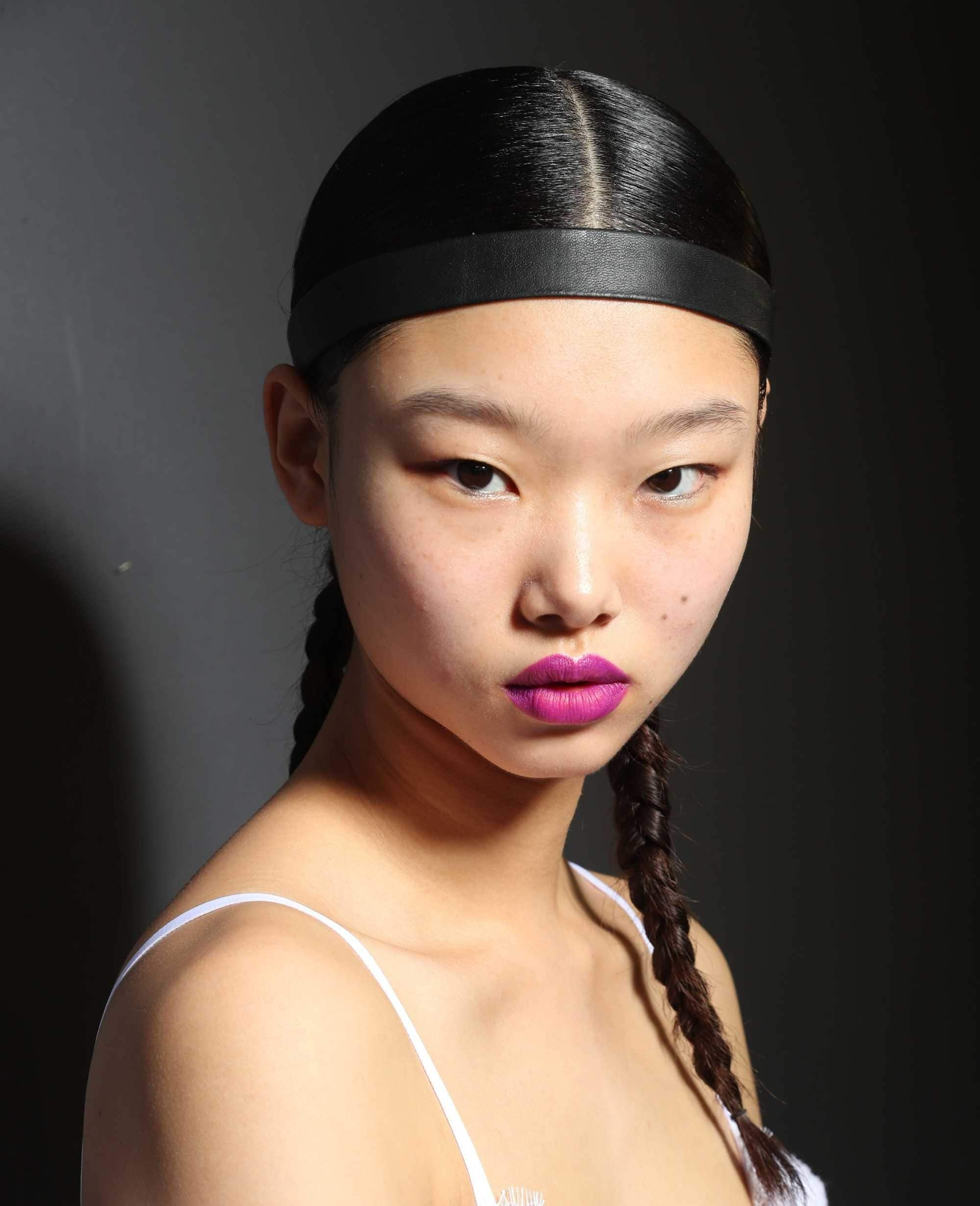 Headband and bandana hairstyles: Close up headshot of a asian woman with dark brown straight hair style in pigtail braids with a black satin strip of ribbon used as a headband