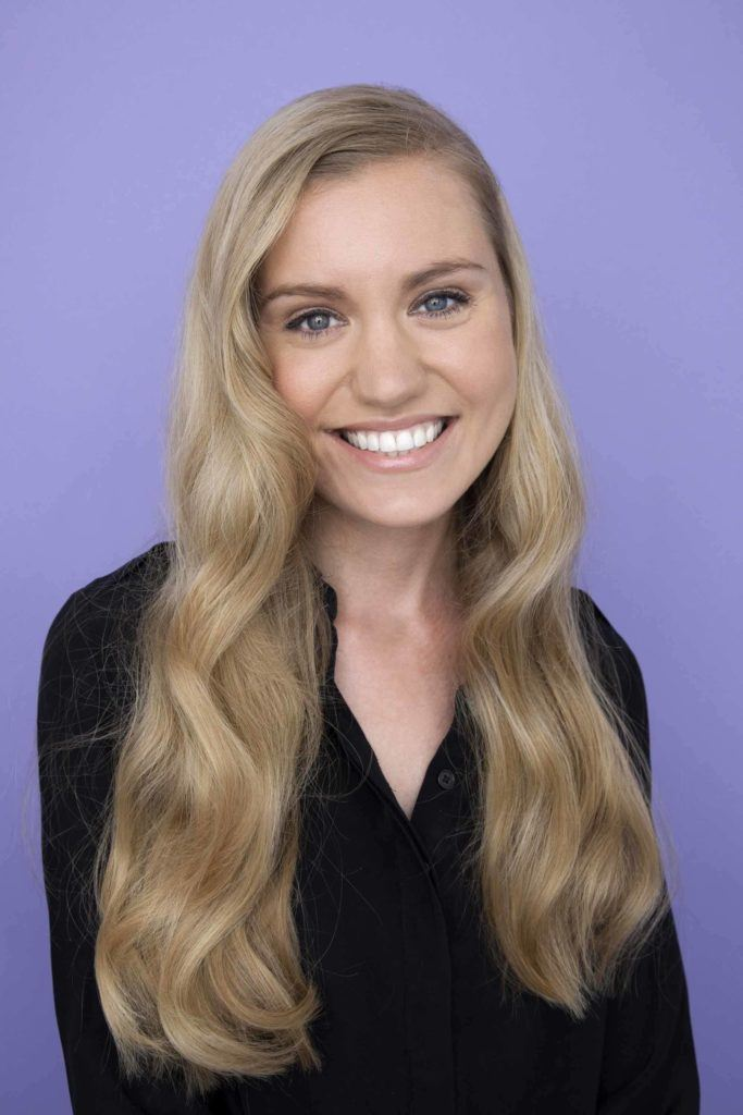 hairstyles for wavy hair: front view of woman with very long blonde hair styled with soft waves in studio