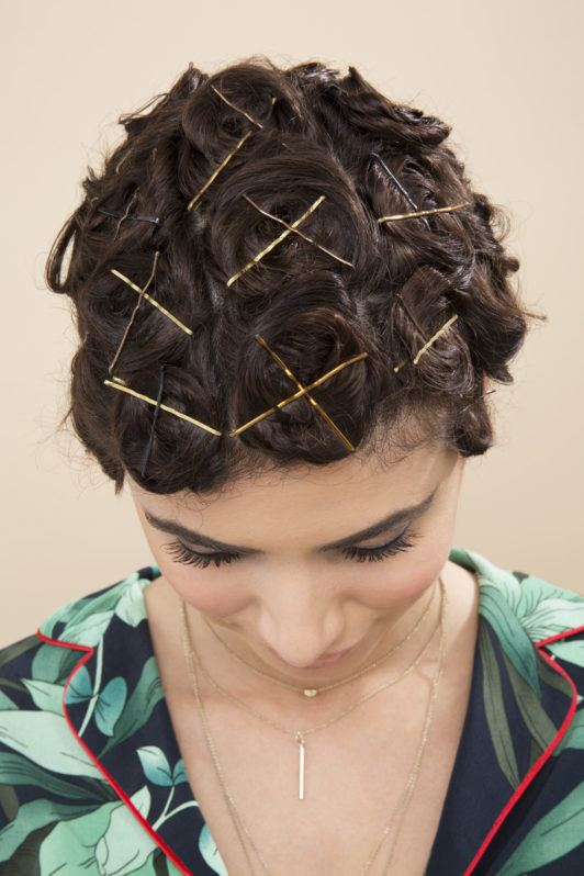 Pin curls tutorial: Brunette model tilting her head down and showing a full head of pinned curls