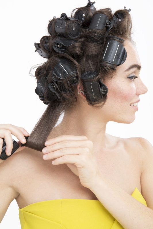 How to use hot rollers: Brunette model with damp long medium brown hair wearing a yellow jumpsuit starting to roll a heated roller