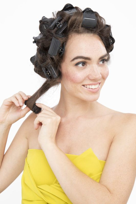 How to use hot rollers: Brunette model with damp long medium brown hair rolling a heated roller and leaving it too cool