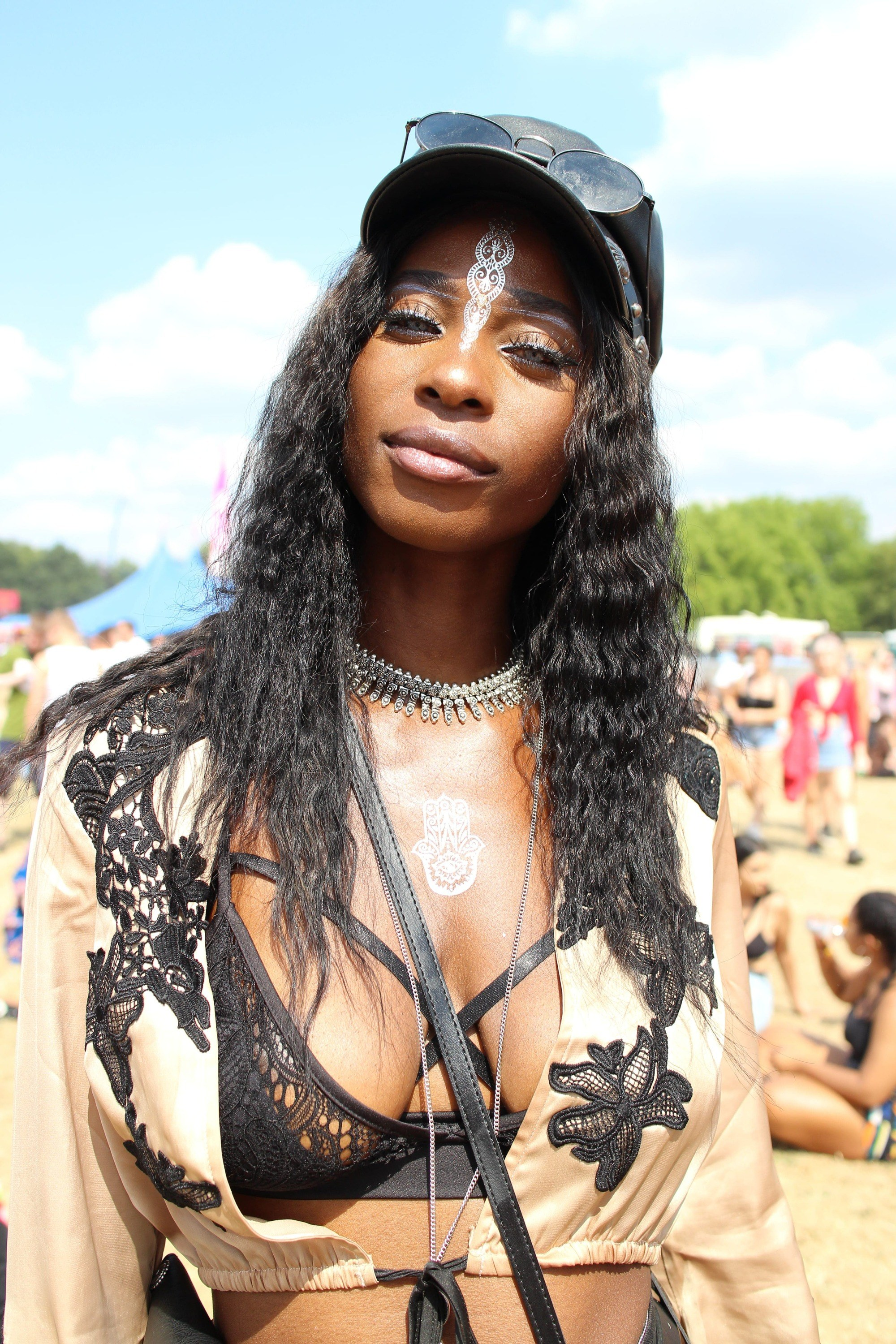 Festival hair accessories: Woman with long dark brown wavy hair styled with a black cap with sunglasses sitting on top
