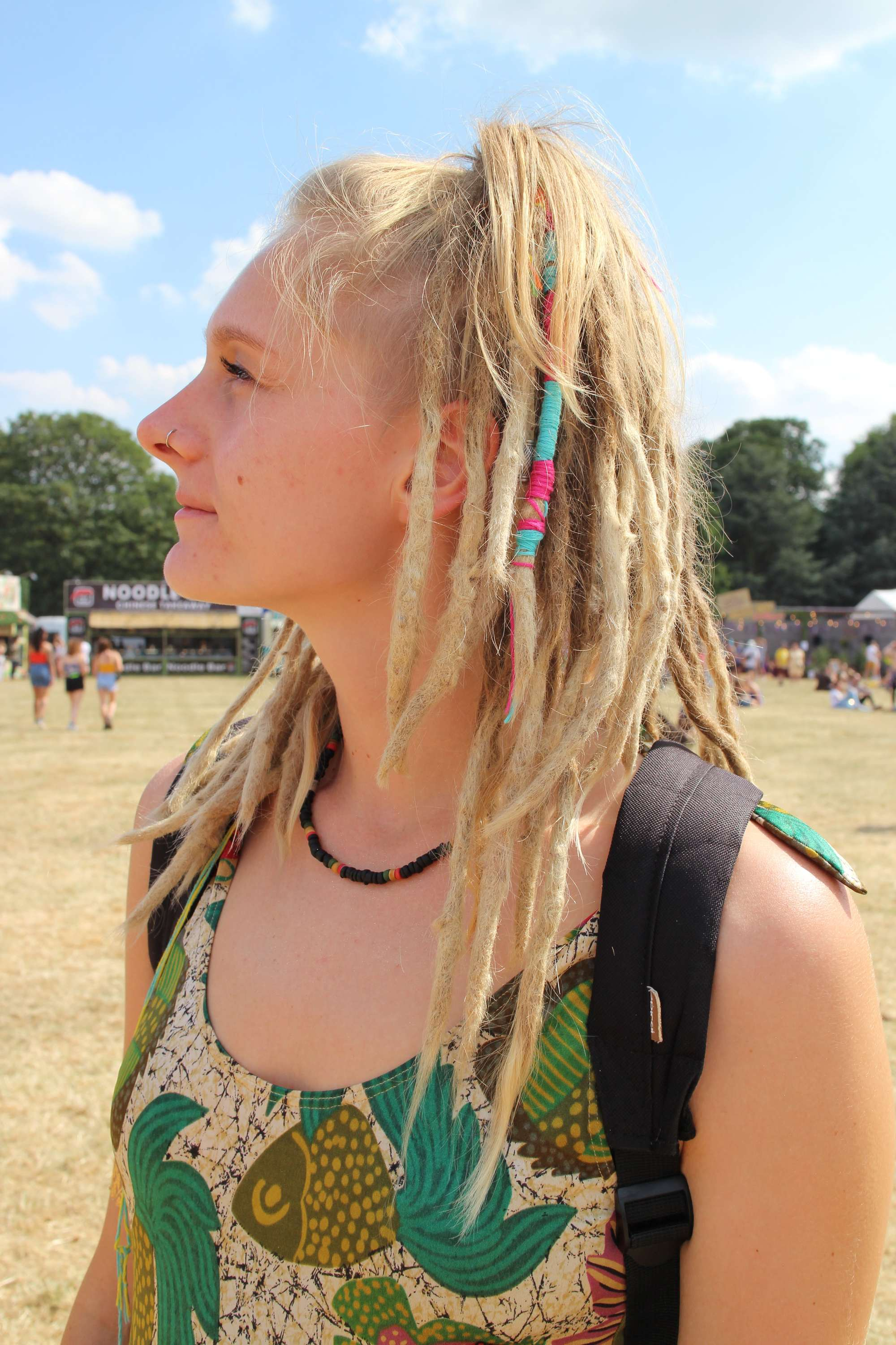 Festival hair accessories: Side view of blonde woman with hair in high ponytail with some strands covered with a blue hair wrap