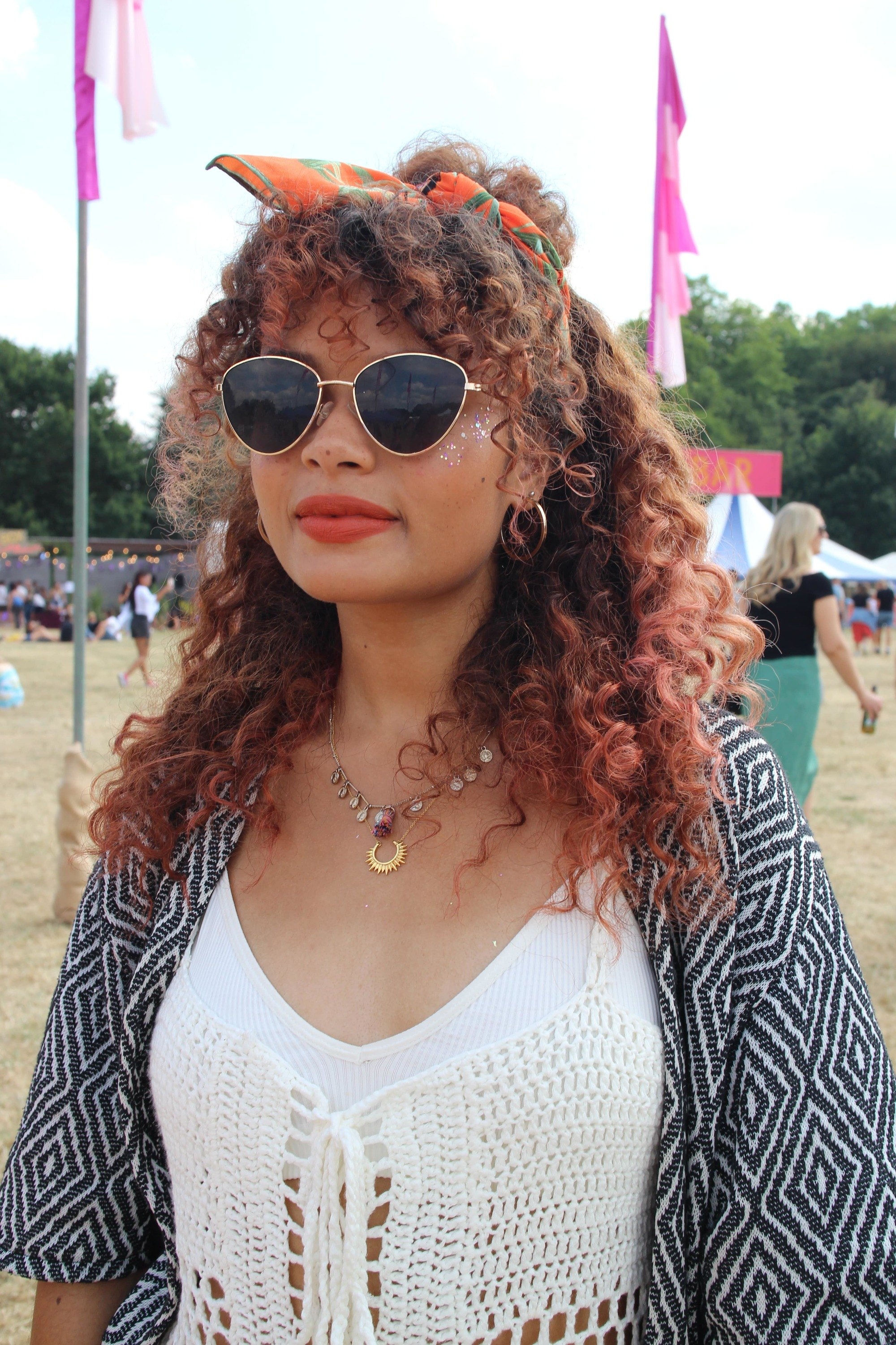 Festival hair accessories: Woman with naturally curly hair styled in a half-up, half-down bun wrapped in a headscarf