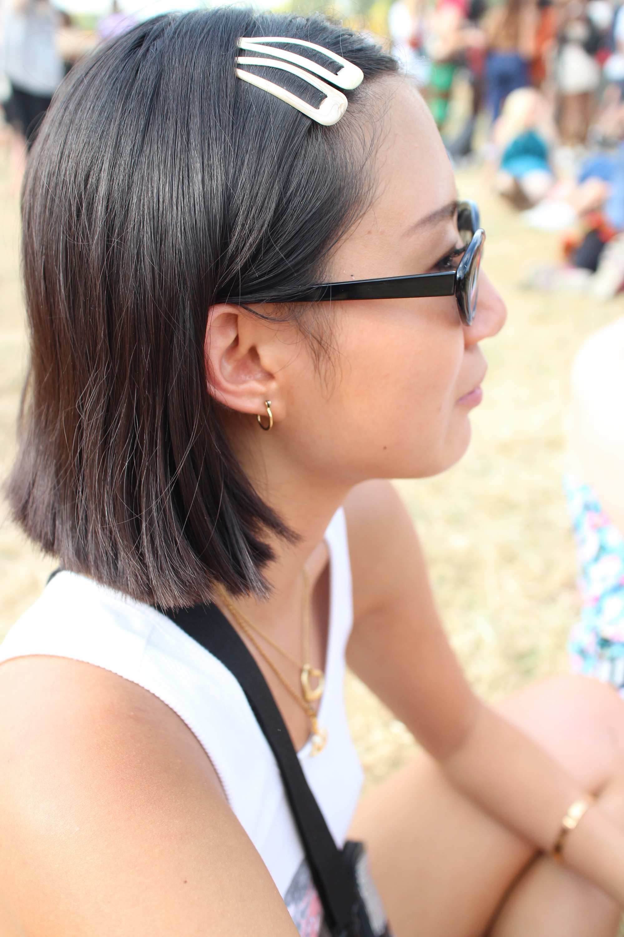 Festival hair accessories: Side view of woman with dark brown bob length hair styled with bright snap clips wearing sunglasses sitting on the grass.