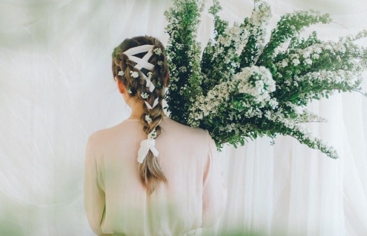 brunette with a ribbon braid holding flowers