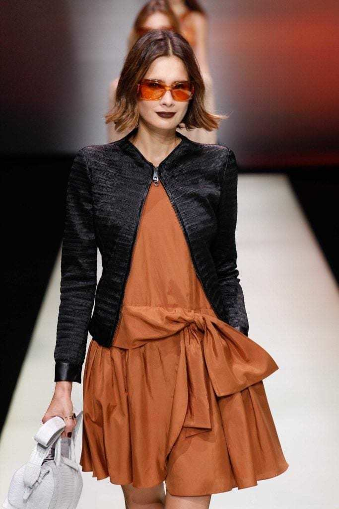 Short ombre hair: Woman on runway with brown pumpkin ombre bob haircut wearing sunglasses.