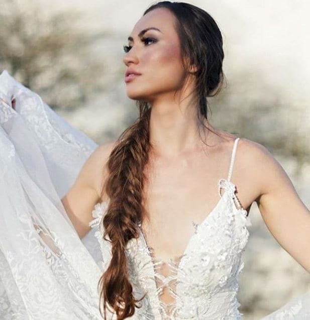 Wedding updos for long hair: Front facing shot of a bride with long chestnut brown hair styled into a fishtail braid, wearing a wedding dress and posing outside.
