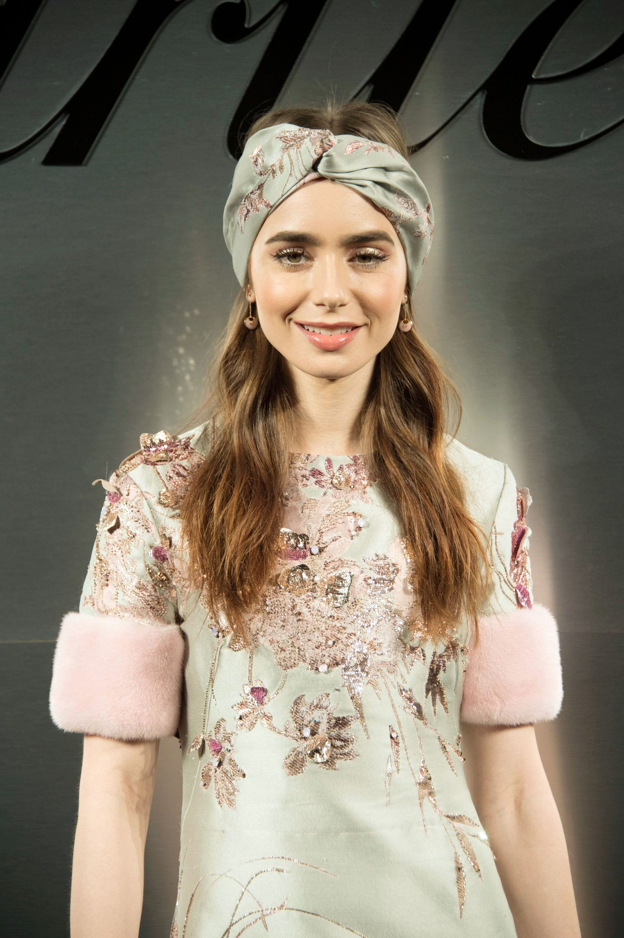 Headband and bandana hairstyles: Lily Collins long wavy light brown hair with turban style headband at red carpet industry event.