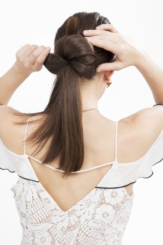 Hair donut: model with long straight brown hair adding donut to base of ponytail