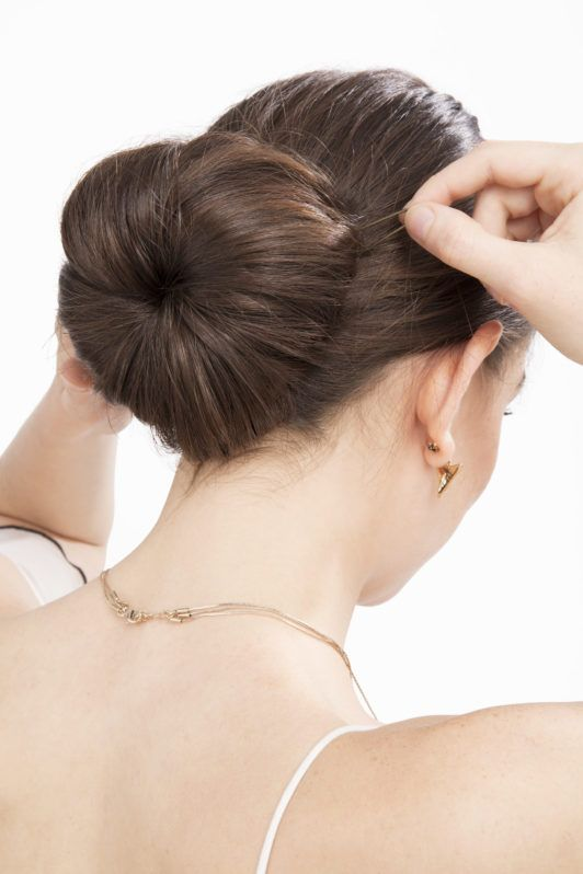 Hair donut. Model with long straight brown hair securing hair donut with pins