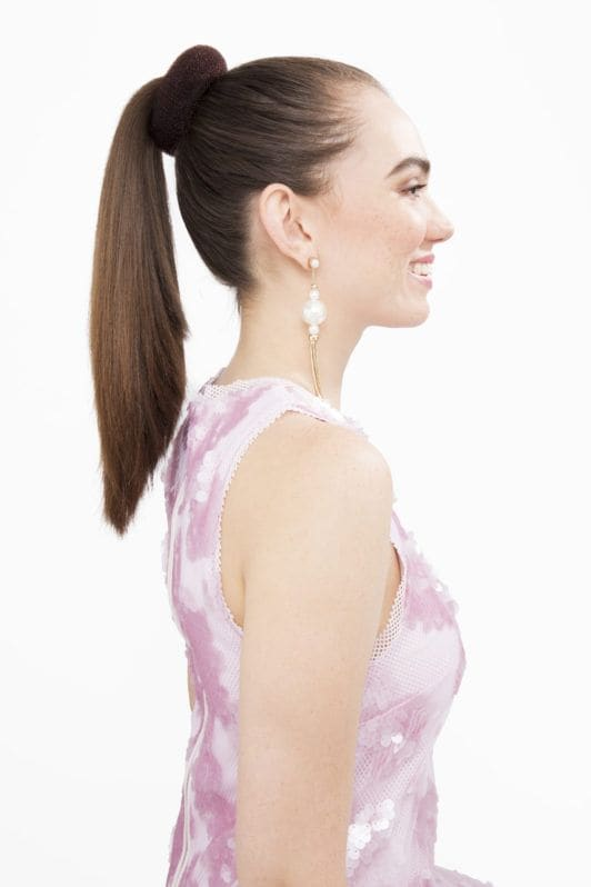hair donut. model with long brown hair with hair donut at base of ponytail