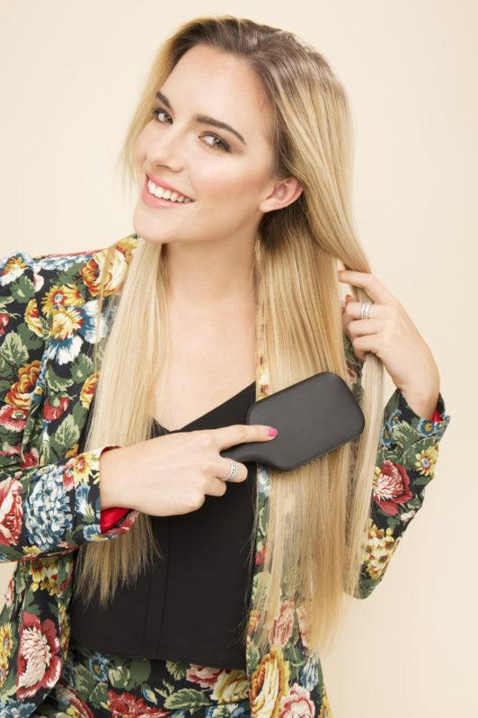 blonde model wearing a floral jacket brushing her hair with a hair brush