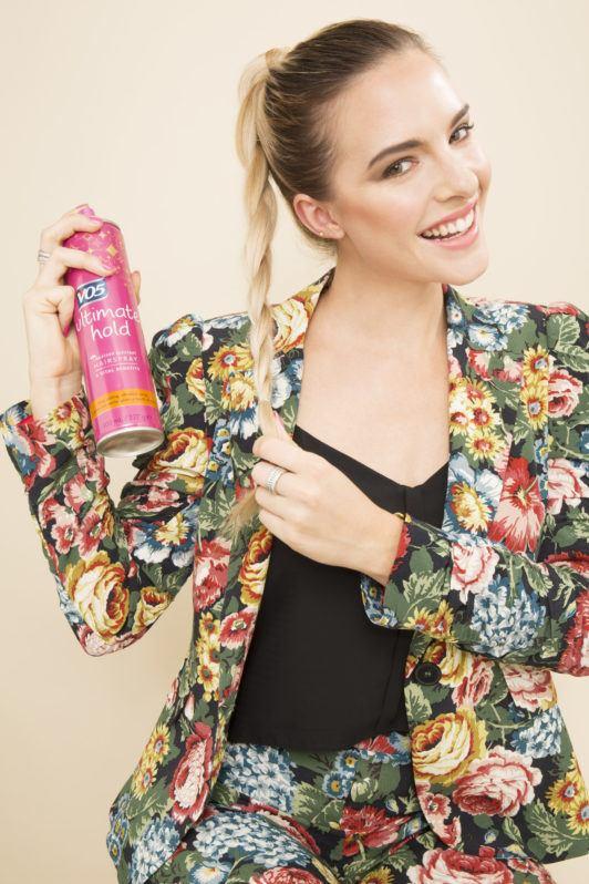 blonde model spraying her ponytail braid with hairspray