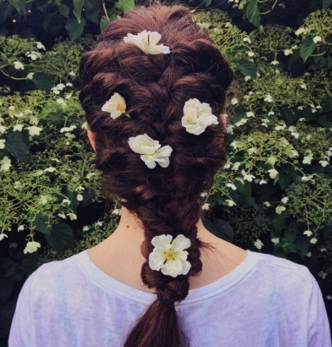 woman with red brown hair in a braid with flowers