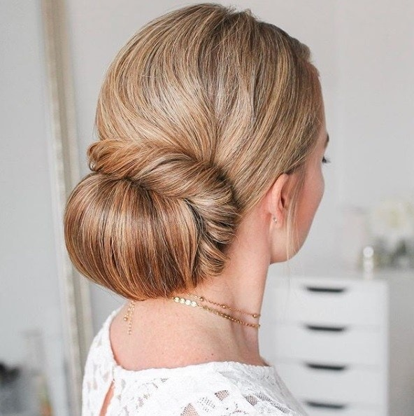 Wedding updos for long hair: Back shot of a woman with long dirty blonde hair styled into a low, half wrapped bun, wearing white dress and posing in a bedroom setting.