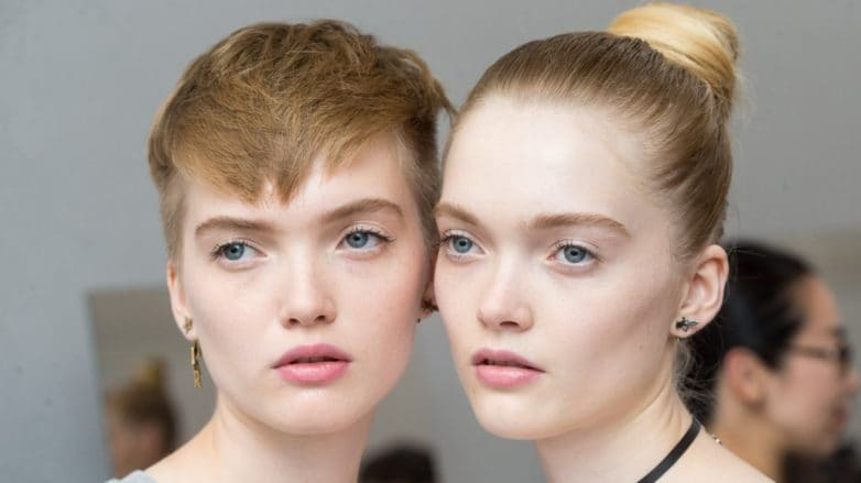 two models, one with a pixie cut and one with long hair in a high bun