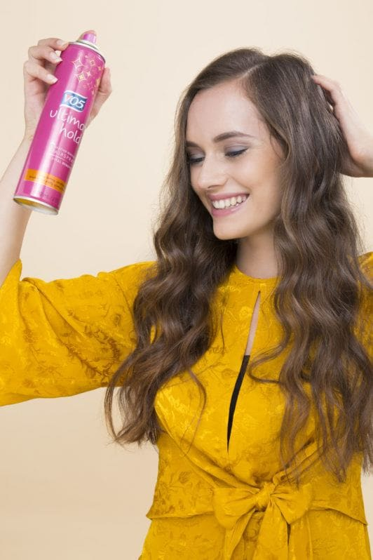 Overnight curls tutorial: medium brown hair model with long curly hair spraying hairspray