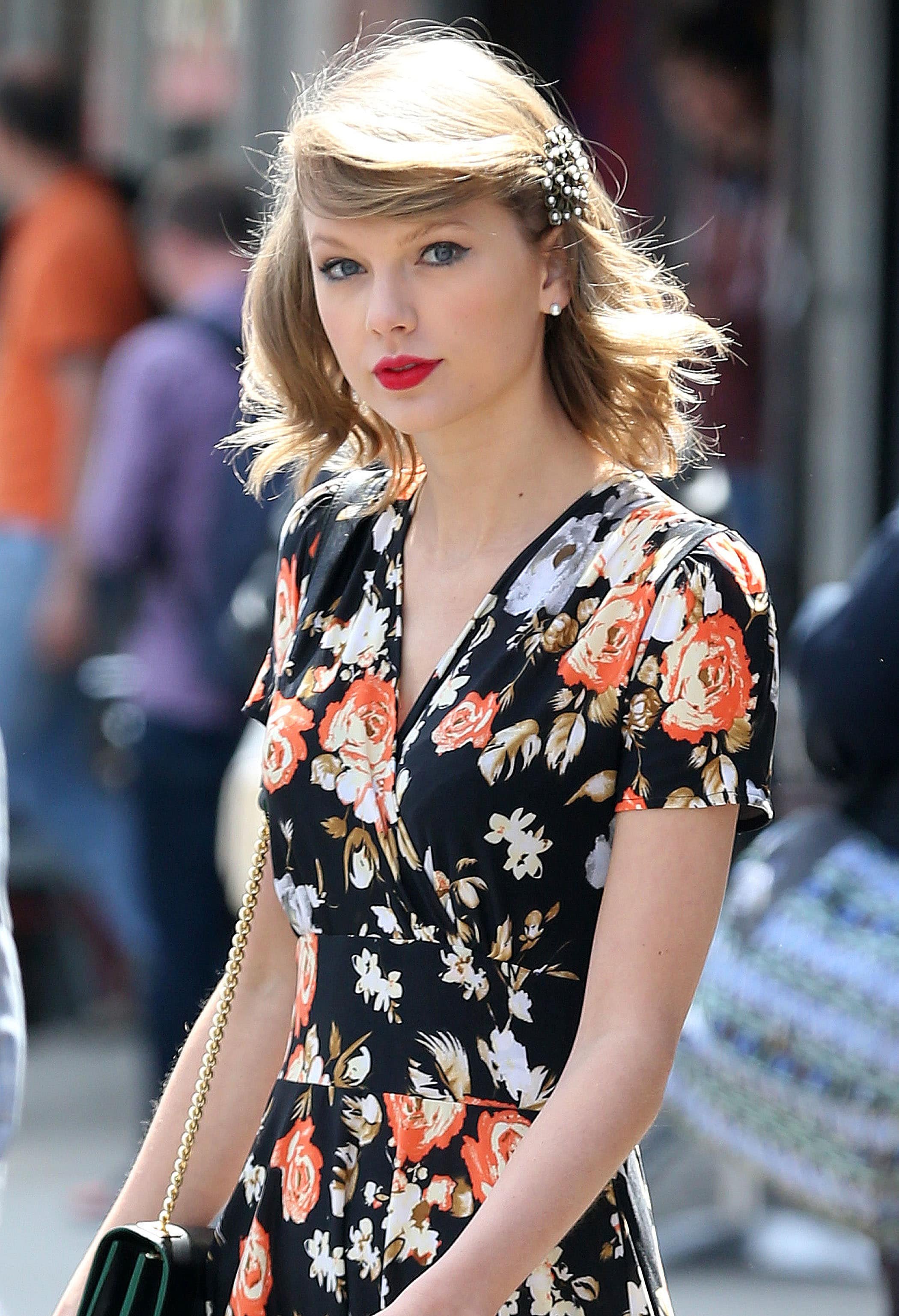Taylor Swift with blonde medium length hair and side swept bangs