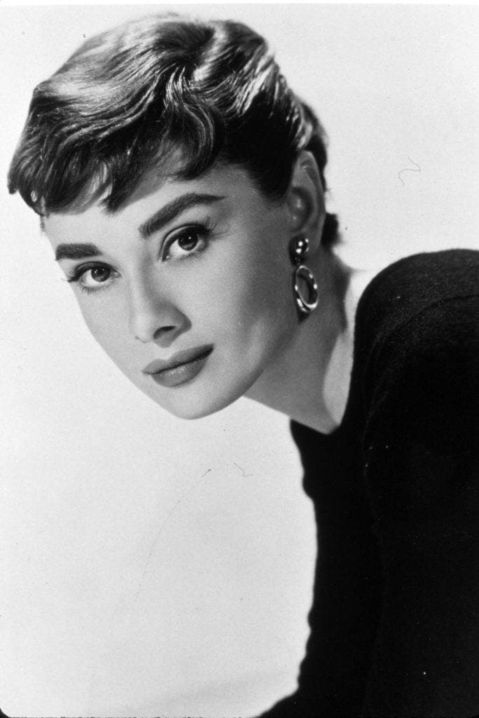 1950s hairstyles: image of Audrey Hepburn with a micro fringe and drop earrings