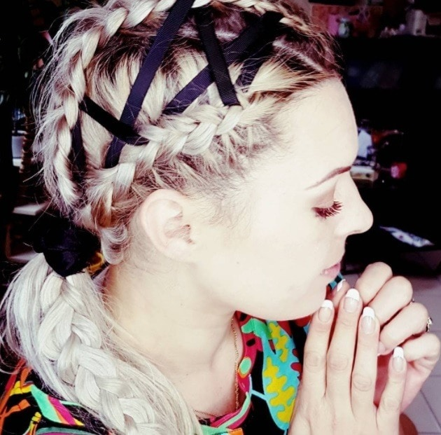 woman with corset ribbon braids weaved into a braided low ponytail