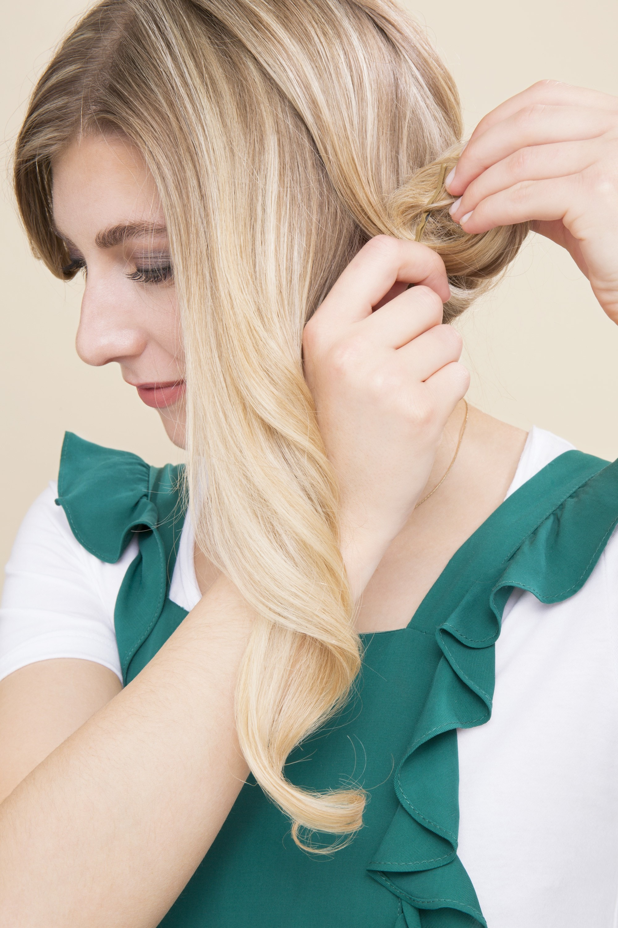 Pin curl tutorial: Blonde woman rolling her hair into a pin curl