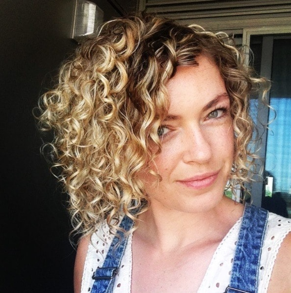 woman with blonde curly bob length hair with dark roots