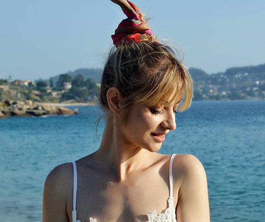 hairstyles for greasy hair: woman with scarf bun updo wearing white
