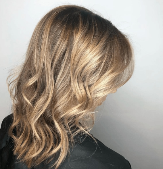 Image of the side of a woman's hair worn long and wavy - dirty blonde hair