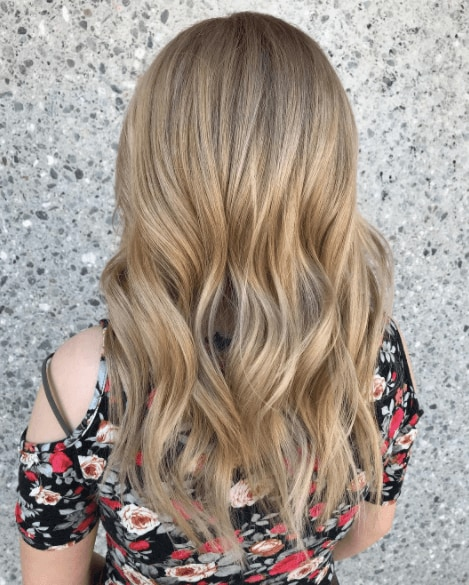 back of a womans head with long wavy hair in a dirty blonde colour