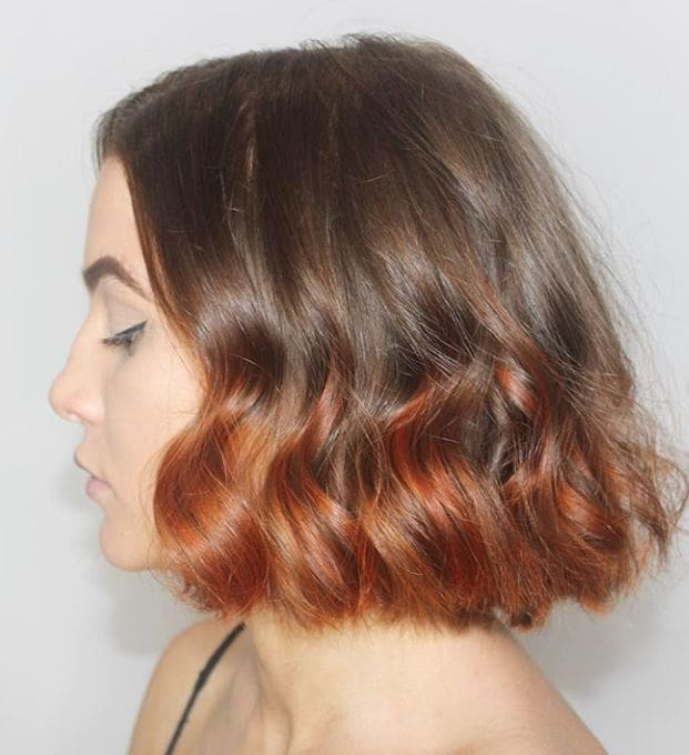 Short ombre hair: Woman with brown curly bob with copper ombre.