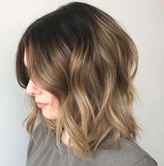 Short ombre hair: Woman with long bob wavy brown soft ombre hair.