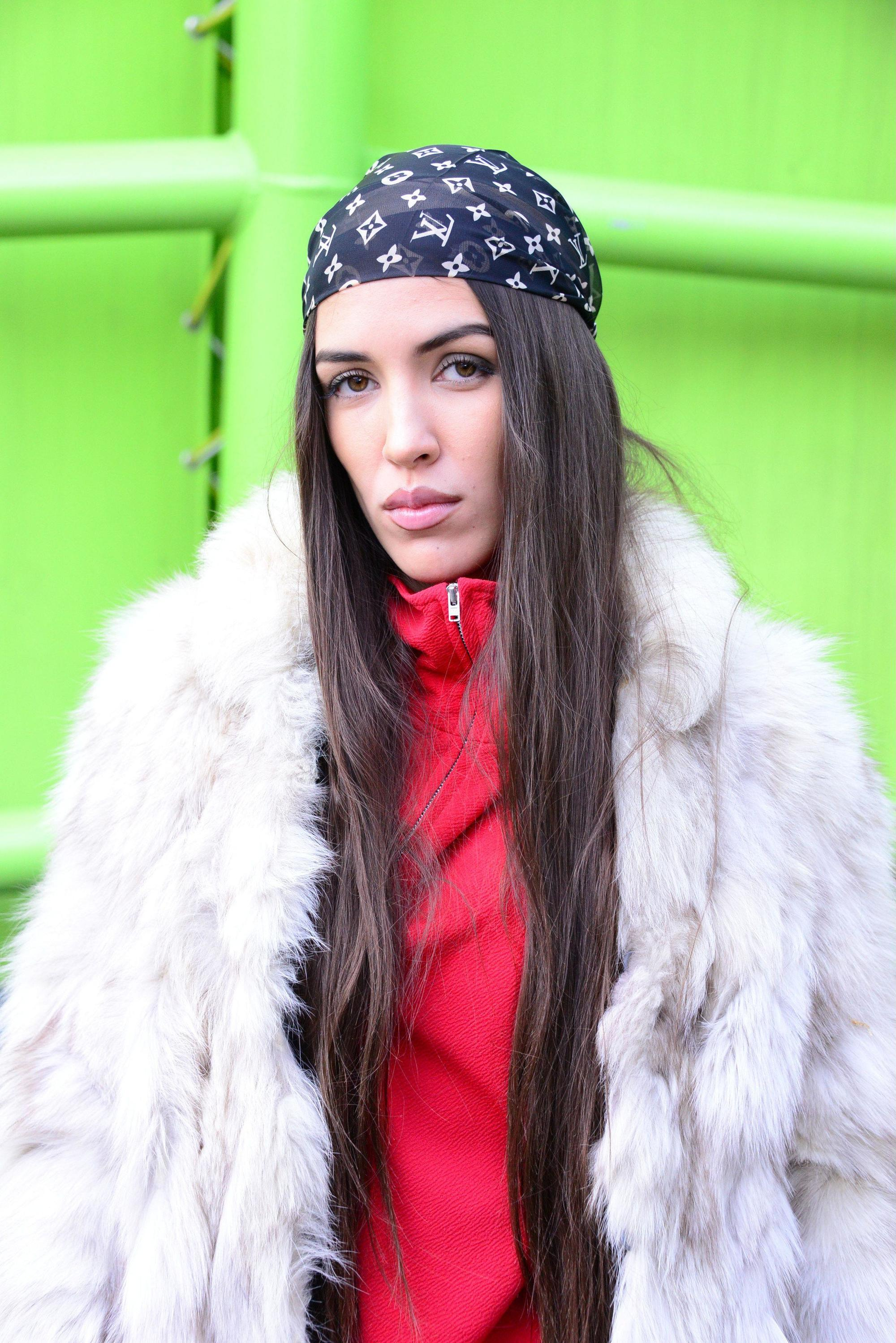 Headband and bandana hairstyles: Street style picture of a woman with long straight brown hair wearing a Louis Vuitton logo print bandana standing against a green backdrop.