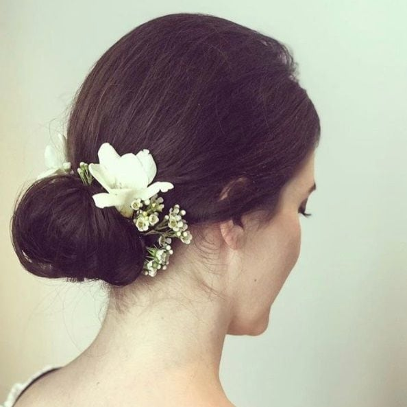 Wedding updos for long hair: Close up shot of a woman with long dark brown hair styled into a simple low chignon updo with a flower hair accessory.