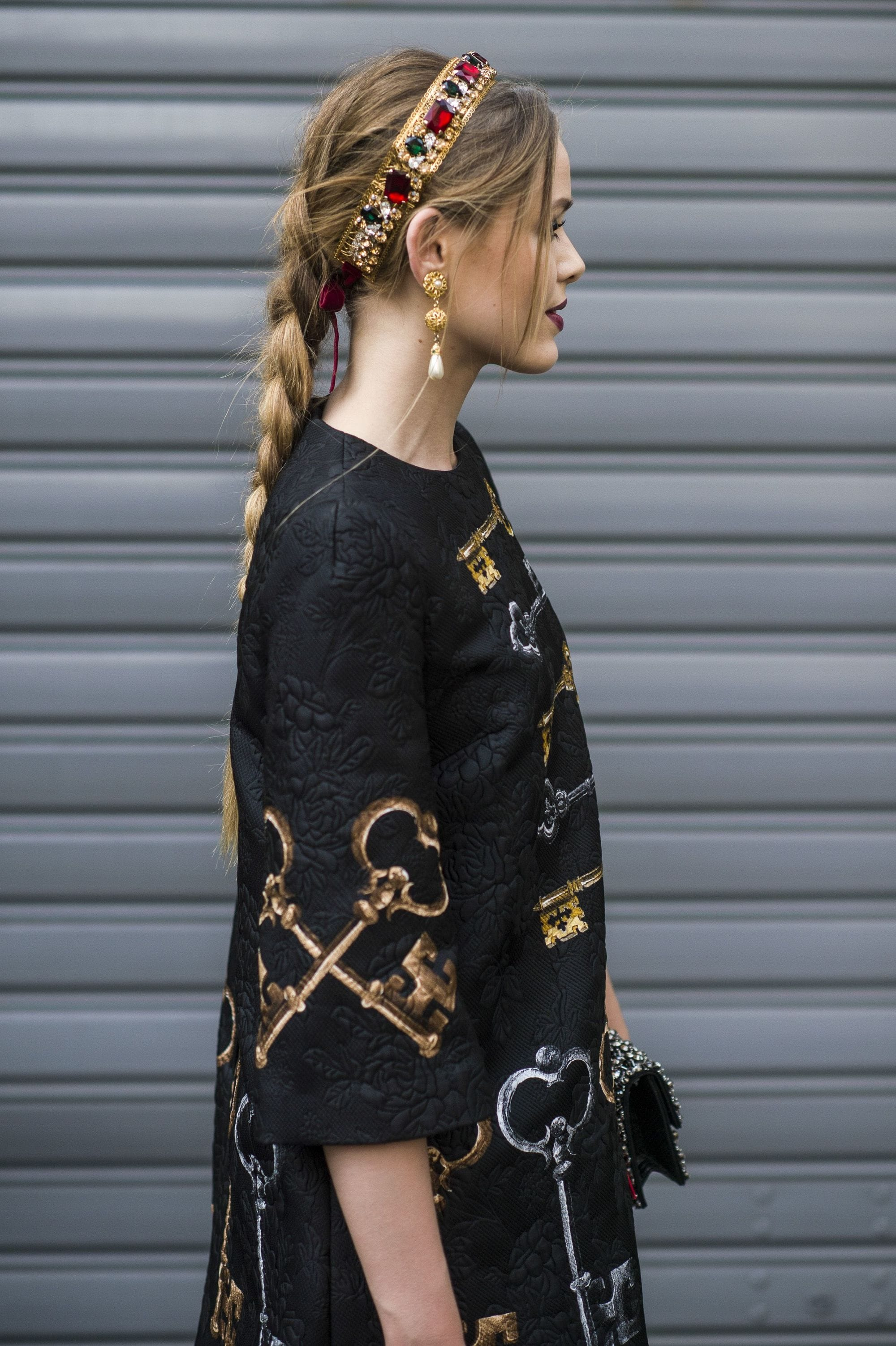 Headband and bandana hairstyles: Side view of a woman with long golden light brown hair styled in a single braid, with a headband and black embroidered dress.