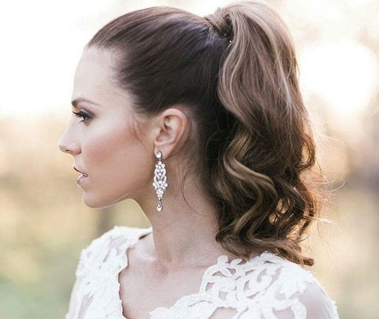 Curly wedding hair: Close up shot of woman in bridal clothing with a high curly ponytail, posing outside
