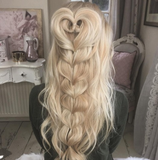 woman with long curly blonde hair in a half-up heart braid