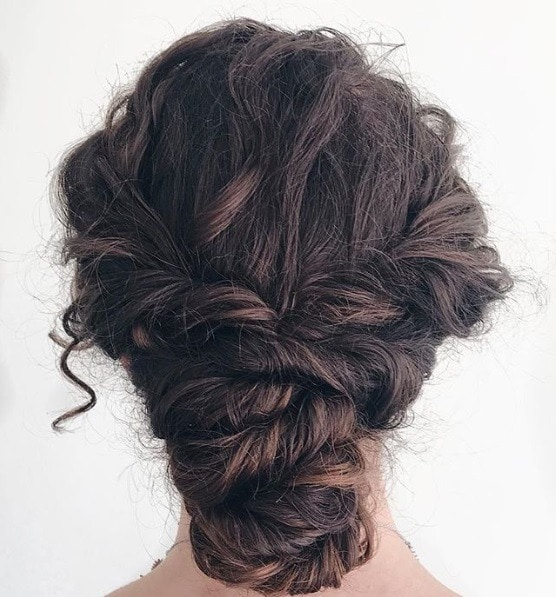 Curly prom hairstyles: Close up back view of a brunette woman with curly hair styled in a twisted braided bun