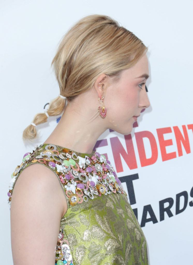 updos for medium hair: side view of saoirse ronan with blonde medium length hair styled in a bubble ponytail