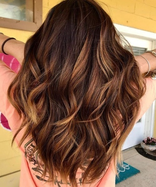 Caramel highlights: Back view of a woman with warm toned caramel highlighted hair, curled into loose waves