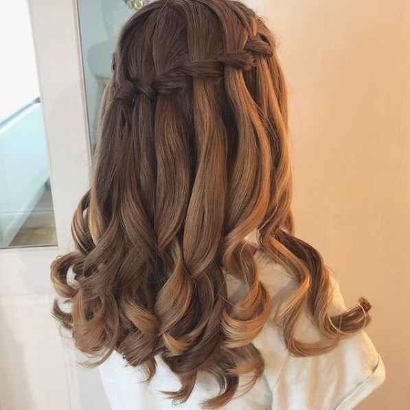 woman with curly brunette hair in a waterfall braid