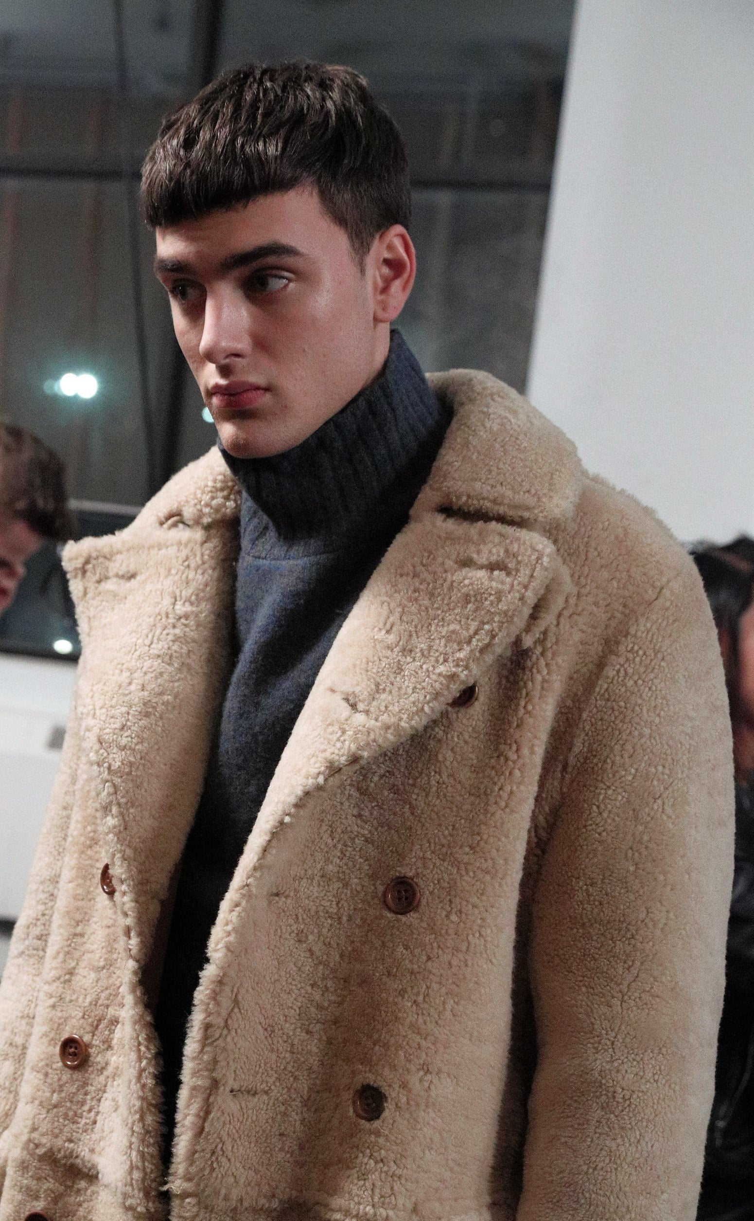 Crop haircut: male model wearing a big winter coat with his hair in a french crop style