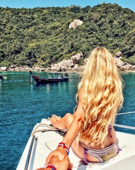 blonde woman sitting on a boat in the sea with long curly blonde beach hair