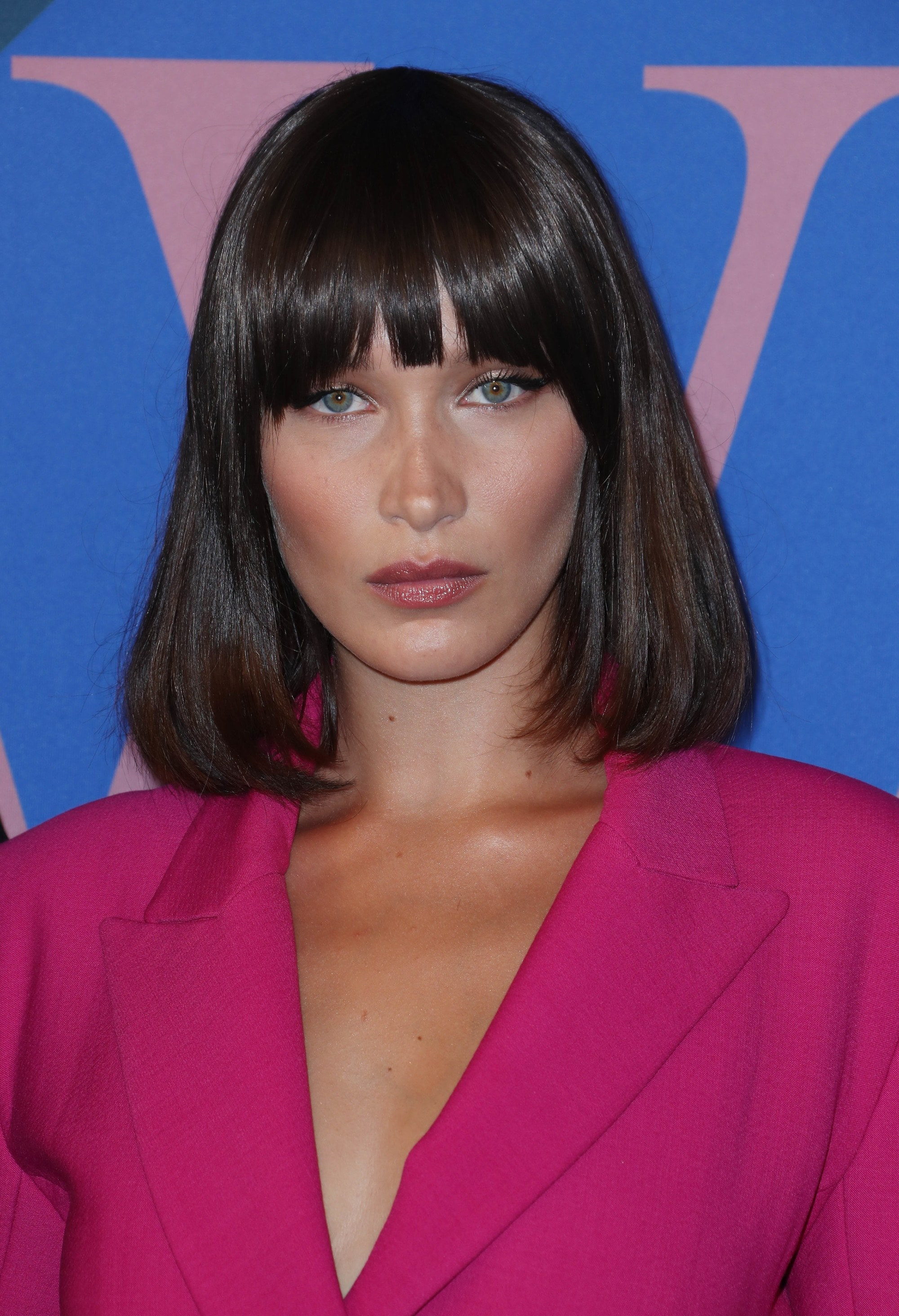 Flat iron hairstyles: Bella Hadid with dark brown hair in curled under Scarface inspired bob and full bangs