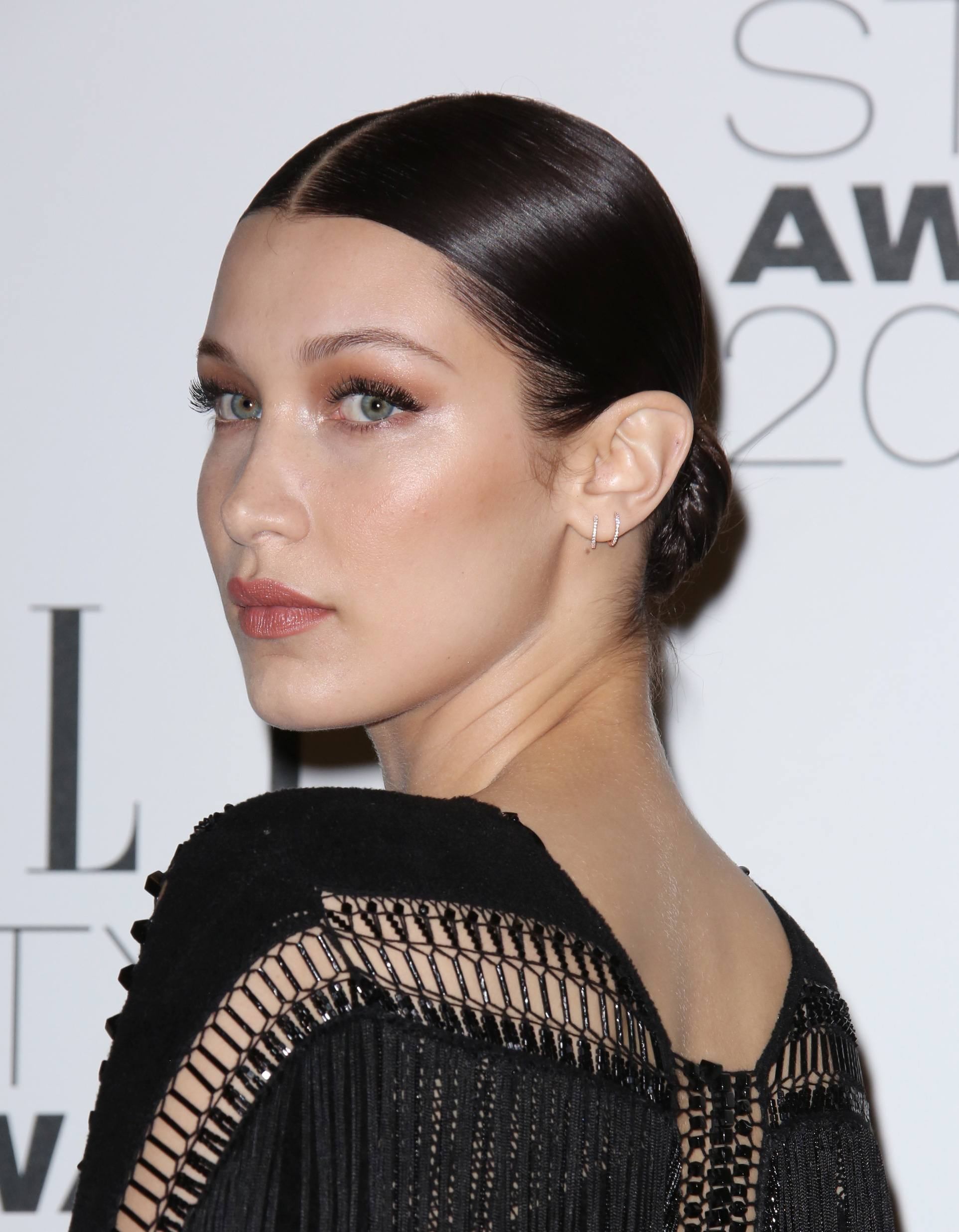 bella hadid with her brunette hair in a sleek low bun