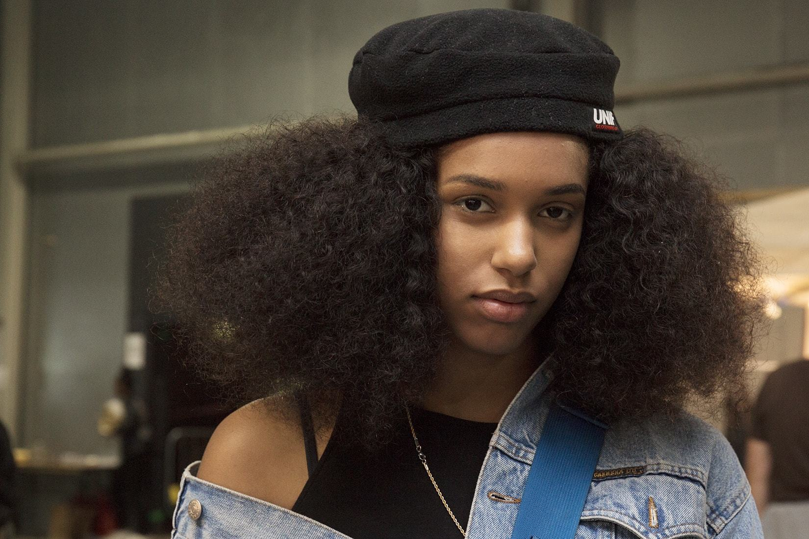 shot of model at afropunk with long afro curls wearing a beret