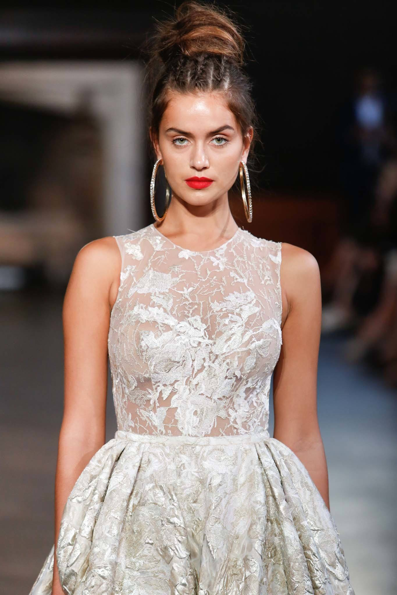 brunette bridal model on the runway with her hair in a high bun with triple cornrow detail