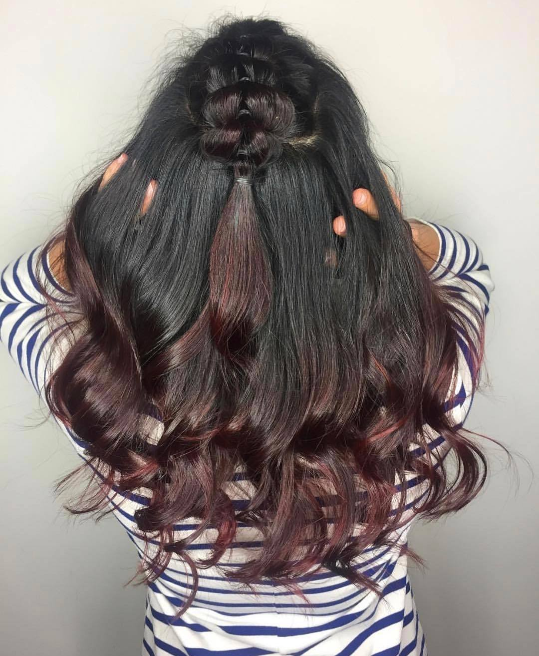 Woman with long curly black to mahogany ombre hair in a half-up pull-through braid